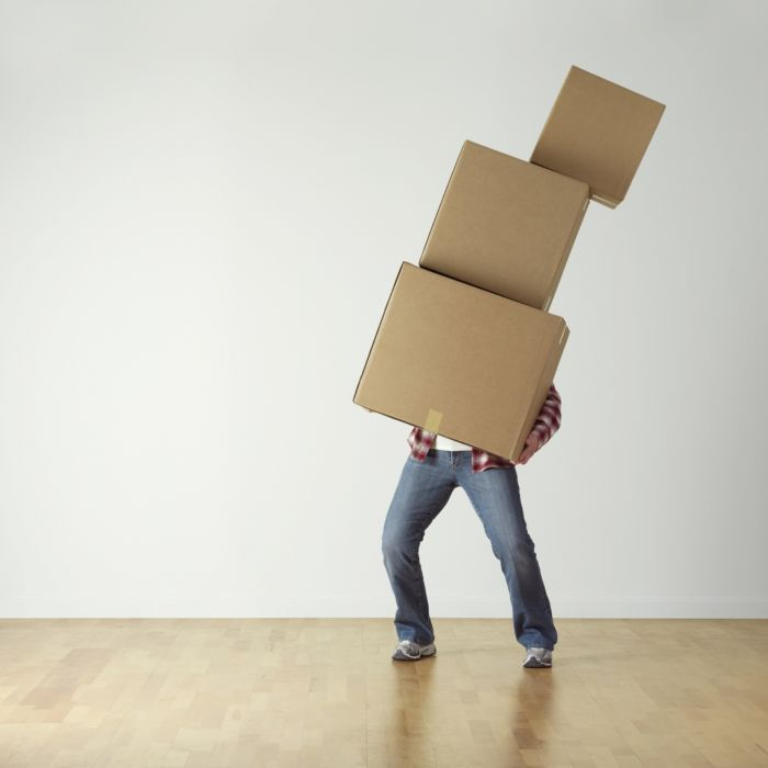 person struggling to carry a leaning tower of boxes